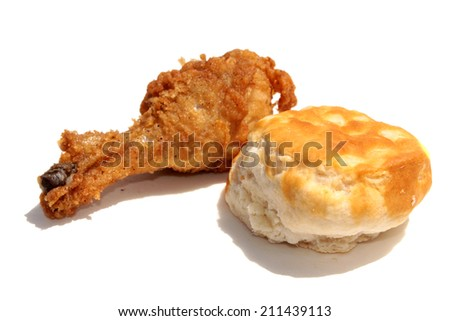 A fried Chicken Leg and Biscuit isolated on white with room for text. Fried chicken is enjoyed by people around the world. Flour Biscuit are good with fried chicken. The perfect Lunch or Dinner image. - stock photo