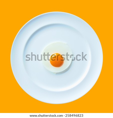 a fried egg on white dish yellow background - stock photo