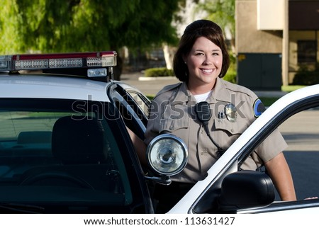 a friendly looking police officer smiles and stands next to her patrol car. - stock photo