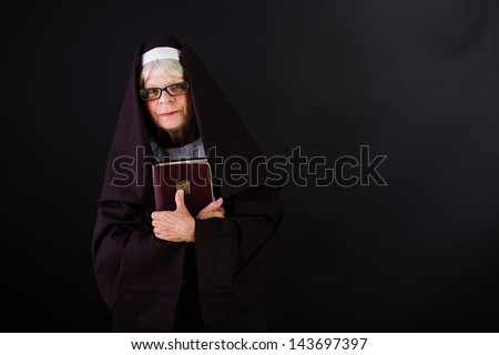 A friendly nun holding her bible - stock photo