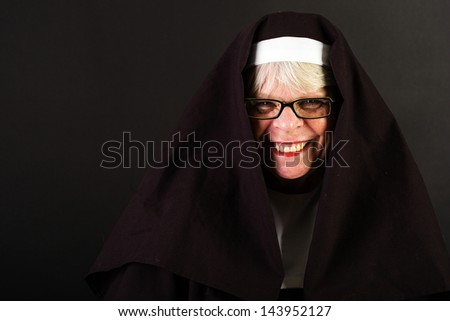 A friendly nun with a happy smile on her face. - stock photo