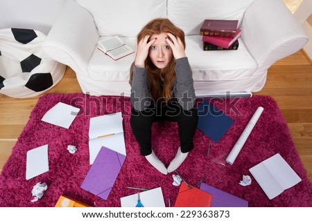 A frightened girl stuck in a room with schoolwork all around - stock photo