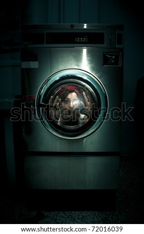 A Frightened Worried And Scared Domestic Housekeeper Woman Becomes Stuck Inside Her Washing Machine When Cleaning In A Crazy And Dark Cleaning Problems Concept - stock photo