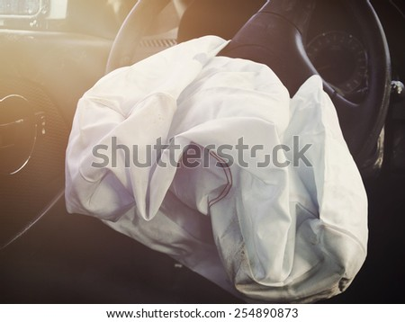 A front car airbag has deflated in a steering wheel from an accident. Use it for a safety or insurance concept. - stock photo