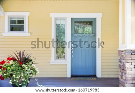 A front entrance of a home with a blue door, yellow siding, and a flowerpot in daytime. - stock photo