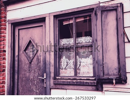 A front of the house. A door and a window with white lace curtain decorated with windmill and tree pattern and wooden hinged shutters . (Amiens, Picardy, France)  Rustic background. Toned photo. - stock photo