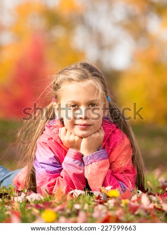 A front portrait of a little girl lying on a colorful leaves in autumn park - stock photo