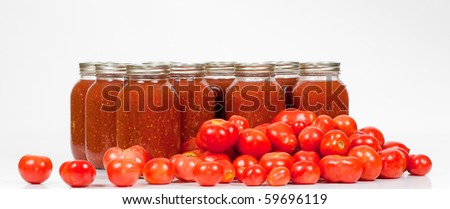 A front studio shot of fresh organic field tomatoes lying in front of homemade canned tomato sauce jars. - stock photo