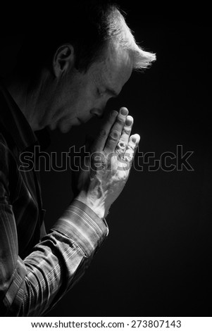 A front view of a man praying in the dark with a ray of sunlight shining down on him. Instagram styling applied. Small amount of added grain. - stock photo