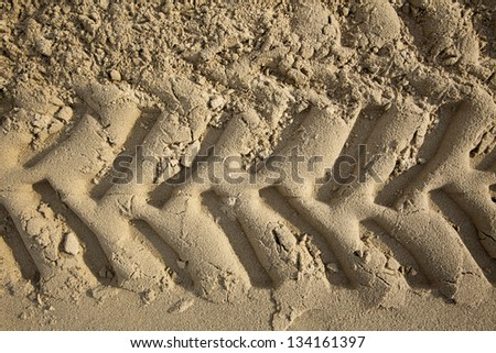 A frontal close up of tractor tire tracks on beach sand. Shot from directly above. - stock photo