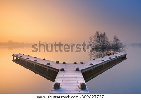 A frosty jetty on a beautiful foggy morning in winter. Photographed in the Amsterdamse Bos (Amsterdam Forest) at sunrise. - stock photo