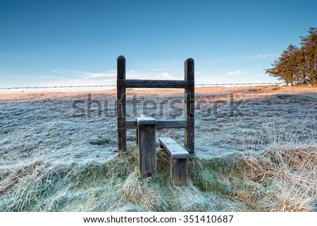 A frosty stile over a barbed wire fence on a cold winter morning on Bodmin Moor in Cornwall - stock photo