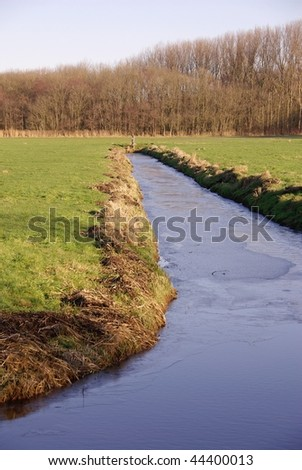 A frozen ditch between the fields - stock photo