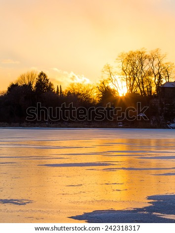 A frozen lake at sunset with copy space - stock photo
