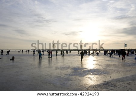 A frozen lake in the Netherlands with people skating - stock photo
