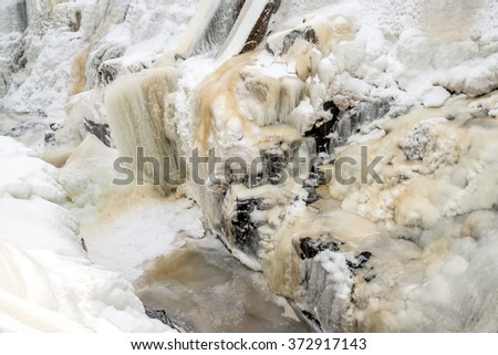 A frozen waterfall. The ice is dirty with traces of mud in it. There are large ice formations and icicles. This is the falls in Saint George, New Brunswick, Canada. - stock photo