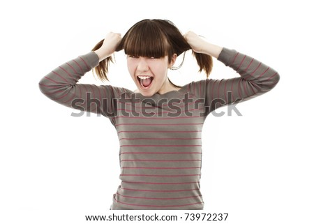 A frustrated and angry girl is screaming out loud and pulling her hair. - stock photo