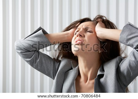 A frustrated businesswoman disarranging her hair - stock photo