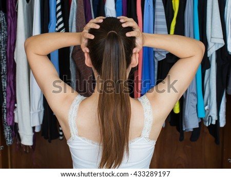 A frustrated young woman standing in front of her closet, trying to decide on her best outfit for a night out with her friends. - stock photo