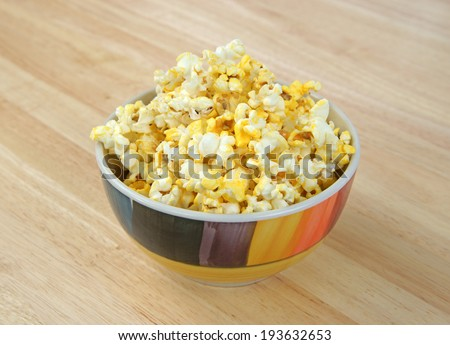 A full bowl of buttered popcorn on a wood table top. - stock photo