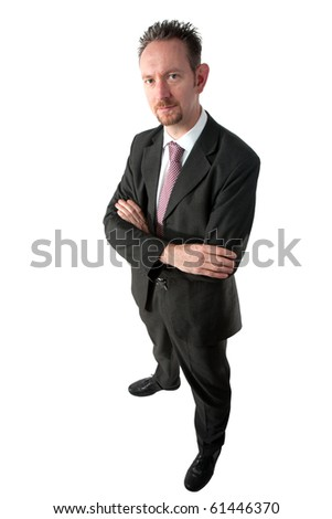 A full length of a mid thirties business man.  The man is wearing a dark grey suit and tie.  The man is looking at camera and has spiky brown hair and a goatee beard.   He also has his arms crossed. - stock photo