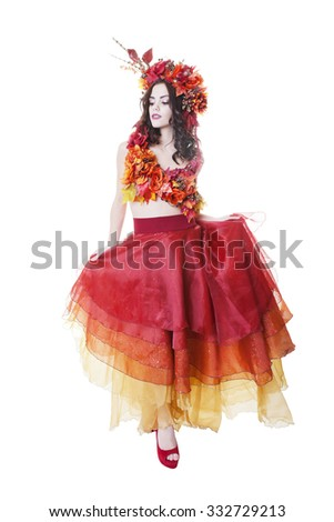 A full-length shot of a model dressed in a multi-tiered skirt, with top and headpiece of Autumn leaves and flowers.  Shot on white background. - stock photo