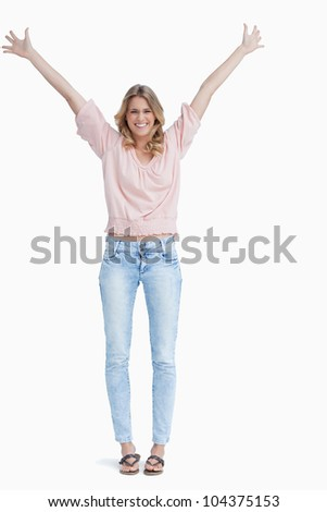 A full length shot of a smiling woman who has her arms raised up against a white background - stock photo