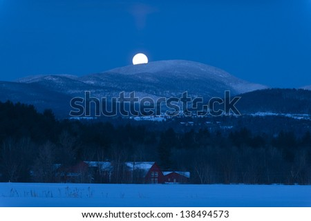 A full moon setting over a mountain behind Trapp Family Lodge, Stowe, Vermont, USA - stock photo