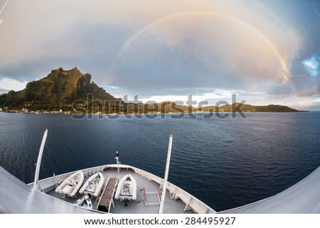 A full rainbow appears over the idyllic tropical island of Bora Bora in French Polynesia. Rainbows often form in the tropics after rain showers.  - stock photo