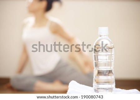 A full water bottle in the foreground while a woman stretches in the background. - stock photo