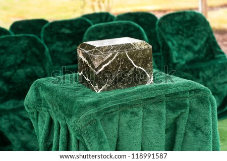 A Funeral Service Scene with a Marble or Granite Urn placed on a Table in front of chairs outside at the gravesite. - stock photo