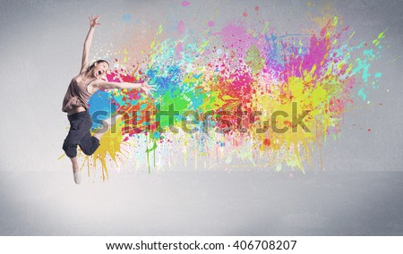 A funky contemporary hip hop dancer dancing in front of grey background with colorful bright paint splatter concept - stock photo