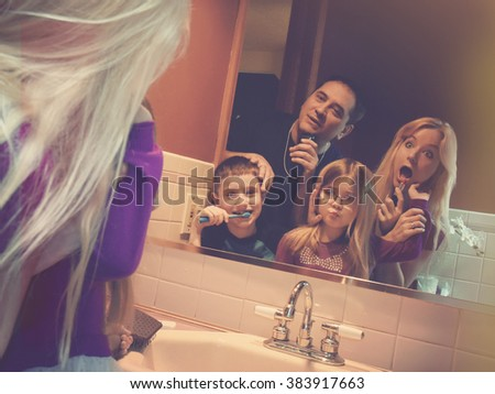 A funny family is getting ready in the morning and rushing in the bathroom in a tight space for a routine, schedule or lifestyle concept. - stock photo