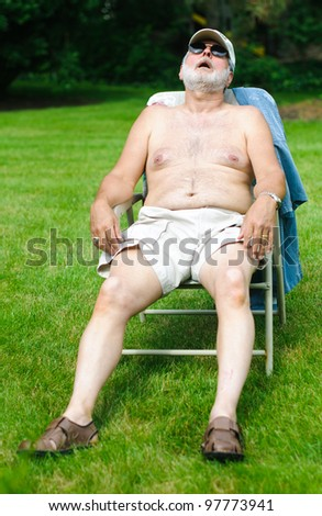 A funny picture of an older shirtless man sleeping in a folding chair. - stock photo
