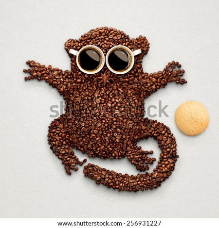 A funny tarsier made of roasted coffee beans, two cups and star anise with an oatmeal cookie. - stock photo