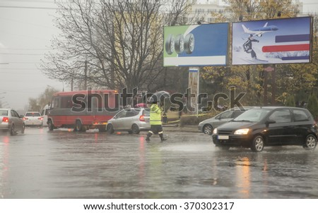 A funny traffic officer under an umbrella walks about cars on road during the rain - stock photo