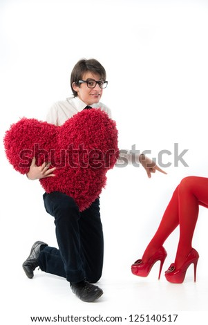 A funny young couple .Nerd,holding  red hairy heart. - stock photo