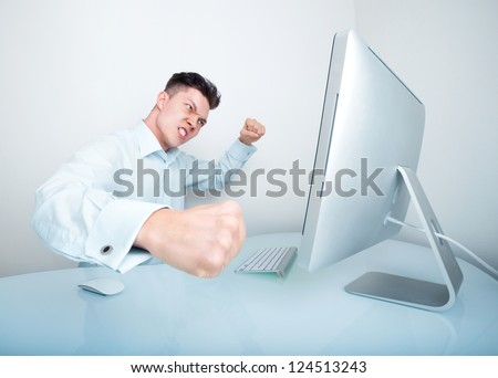 A furious businessman frustrated with his lack of wireless connection and or computer skills takes his anger out by punching his computer - stock photo