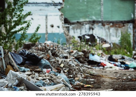 A garbage dump and a building with ruined brick walls at background. Concept of disaster, war. - stock photo