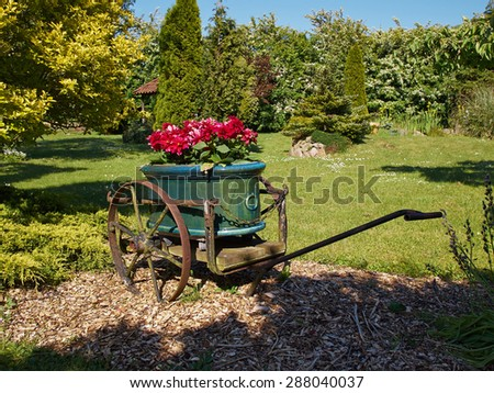 A garden decorated with an old wagon turned into a planter - stock photo