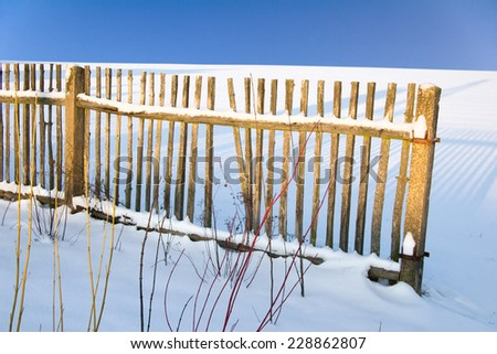 a garden fence in a winter landscape - stock photo