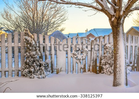 A garden gate decorated with a Christmas wreath all covered in snow. - stock photo