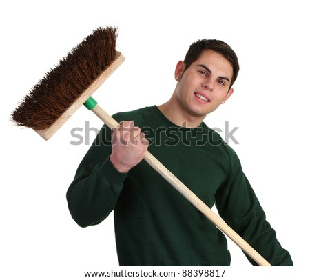 A gardener with a wooden broom in a green jumper - stock photo
