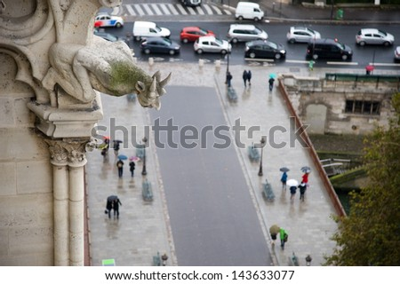 A gargoyle overlooking pedestrians walking in the rain in paris - stock photo
