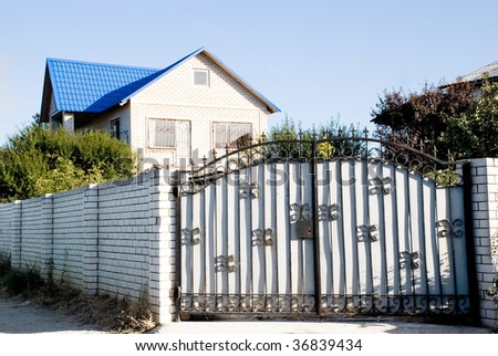 A gate of a modern village courtyard. Real estate related. - stock photo