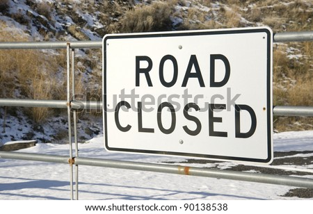 "A gate with a sign that says ""road closed"" found in the dead of winter transportation infrastructure - stock photo"