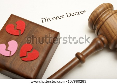 A gavel and broken hearts on top of divorce papers with the focus on the writing. - stock photo