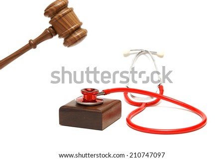 A gavel is about to hammer down on a stethoscope that is resting on the sounding block. - stock photo