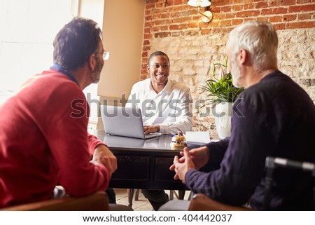 A gay male couple checking in at a boutique hotel, waist up - stock photo