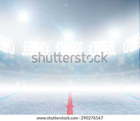A generic ice hockey ice rink stadium with a frozen surface under illuminated floodlights - stock photo